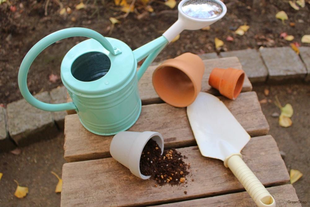 鉢植えと土、スコップ、ジョーロの植物の栽培道具たち