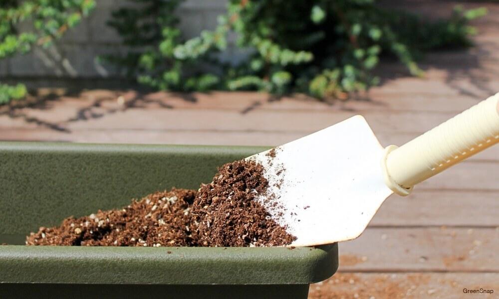 プランターにスコップで土を入れている画像